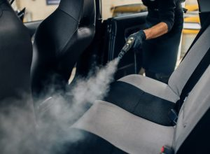 carwash-worker-cleans-seats-with-steam-cleaner-NPY8BSC
