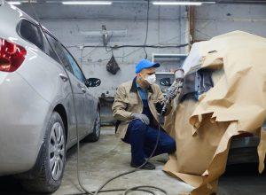 man-in-uniform-painting-car-H96U945